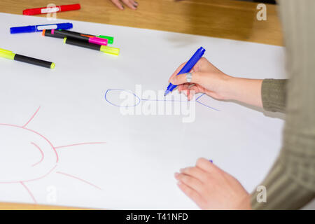 Girl hand with blue felt pen drawing stickman on big white paper on desk in classroom. Colorful pens spilled on paper. Education concept. Close up - Stock Image