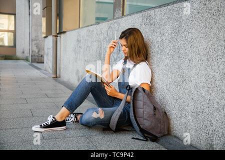 Beautiful teen girl in denim overalls studying sitting on the floor - Stock Image