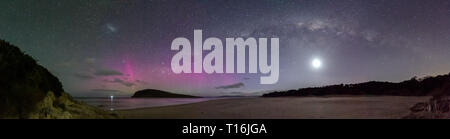 Panorama of the Milky Way with the moon underneath and a disaplay of the Aurora Australis or Southern Lights over a beach in Tasmania. - Stock Image