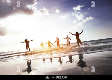 Group of happy peoples runs and jumps at sunset sea beach. Tropical tourism concept - Stock Image