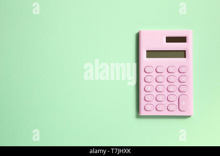 Pink digital calculator on green background - Stock Image