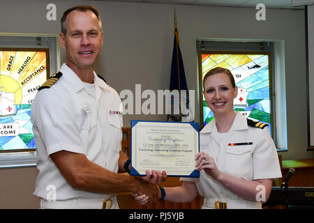 180828-N-IY469-027 – Capt. Devin Morrison, NMCP acting executive officer, presents Lt. Amy Strickman with her graduation certificate. Strickman will be stationed at Naval Hospital Jacksonville. - Stock Image