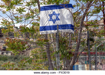 Israeli flag tied to a tree above a wire fence in Jerusalem, Israel - Stock Image