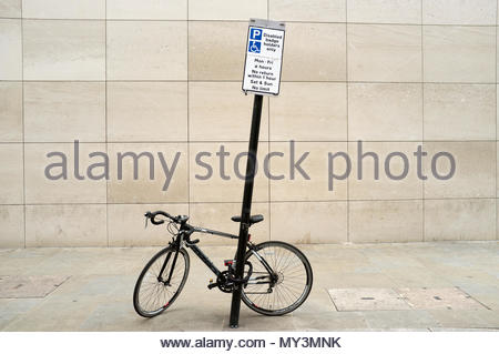 A bicycle padlocked up to a car parking information sign, in Muscovy Street, London, UK. - Stock Image