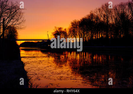 Dramatic and colorful sunrise over a Beautiful early winter landscape with a frozen river or canal, treelined riverside and grass at sunrise creating  - Stock Image