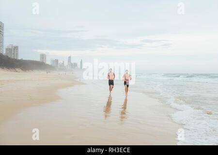 Men running on beach - Stock Image