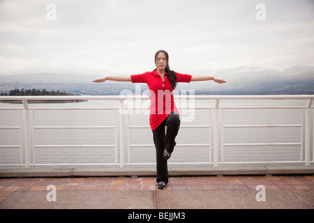 A young Asian woman does the Vrksasana Tree Pose yoga pose with eyes closed at Canada Place, Vancouver, British - Stock Image