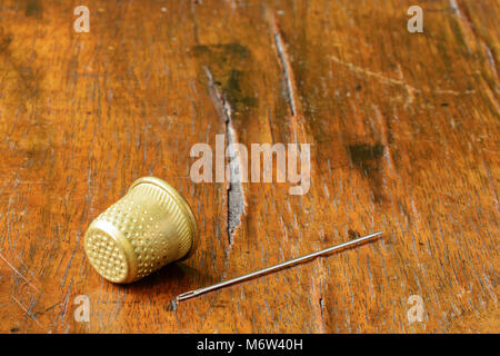 Thimble and a needle on an antique wood veneer full of cracks and scratches. Selective focus. Closeup. There is - Stock Image