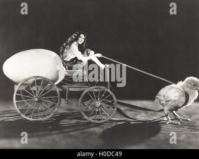 Baby chick pulling cart with woman and giant egg - Stock Image