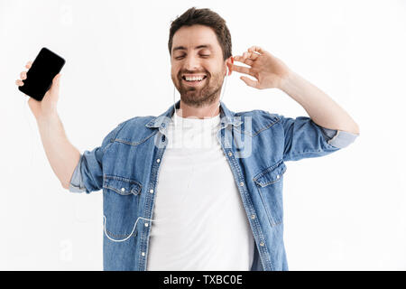 Portrait of a handsome bearded man wearing casual clothes standing isolated over white background, listening to music with earphones, holding blank mo - Stock Image