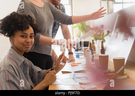 Portrait confident creative designer cutting photographs in office - Stock Image