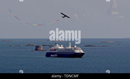 'Cheeky Champ' stunt flying trailing ribbon banner over cruise liner at anchor. - Stock Image