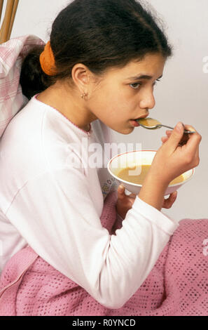 sick child having bowl of soup in bed - Stock Image