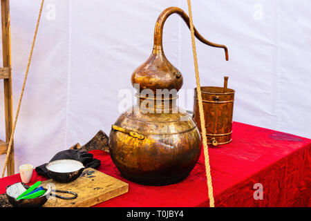 A medieval chemical vessel made of copper. Metal bucket, earthenware on a table covered with red cloth. White canvas in the background - Stock Image