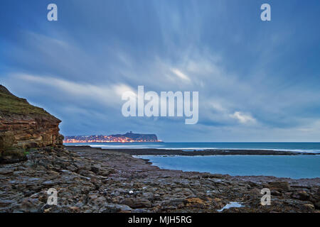 South Bay streetlights illuminate the seafront of Scarborough's headland under swirling clouds in pre-dawn light. - Stock Image