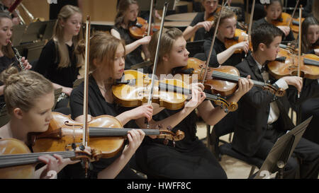 High angle view of student musicians playing violins in orchestra recital - Stock Image