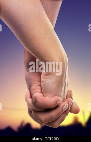 Closeup of couple holding hands with sunset background as romantic relationship concept isolated on white studio background - Stock Image