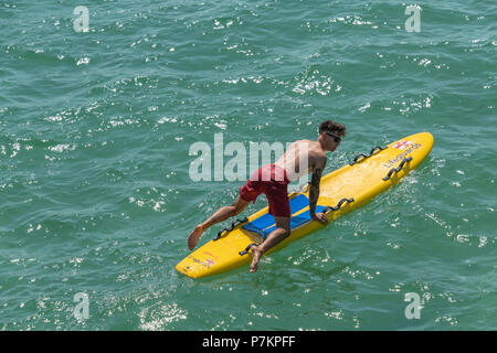 Bournemouth, UK. 7th July 2018. RNLI lifeguard on a surf board in Bournemouth. Credit: Thomas Faull / Alamy Live News - Stock Image