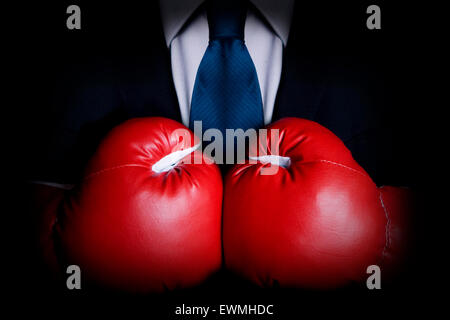 Stock image of person wearing business suit and boxing gloves - Stock Image