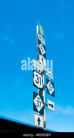 Highway direction signs with arrows to North, South, and West, M72, US31, M37 highways, and Lake Michigan Circle Tour sign - Stock Image