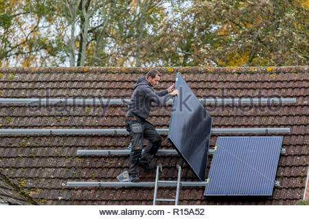 A workman installing solar panels on the roof of a house - Stock Image