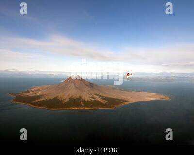 A helicopter approaches the Augustine Volcano carrying a team of geologists on Augustine Island in the lower Cook - Stock Image