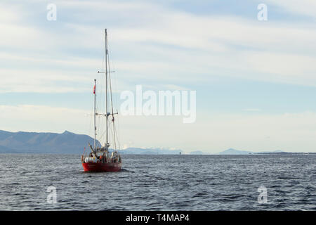 A red sailing boat against snow capped mountains, Norway - Stock Image