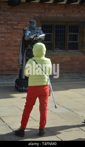 A tourist looks at a living statue on Henley Street, Stratford upon Avon, Warwickshire - Stock Image