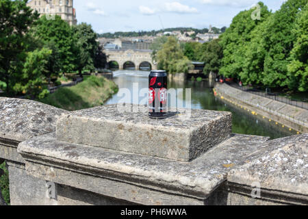 A can of cider left on the parapet of the North Parade bridge in the city of Bath with the Pulteney Weir and bridge in the background - Stock Image