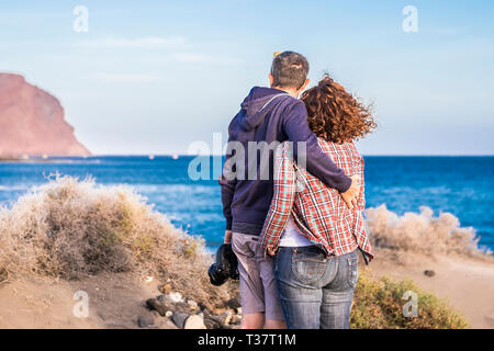 Adult caucasian couple viewed from back hug with love enjoying and looking the ocean and the coast during vacation - tourist and tourism concept with  - Stock Image