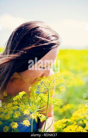 Young woman smelling yellow flower - Stock Image