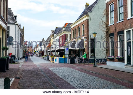 People dine outdoors at the Restaurant and Partycentrum De Haas, as pedestrians stroll on Jufferenstraat in the ancient city of Elburg, Netherlands. - Stock Image