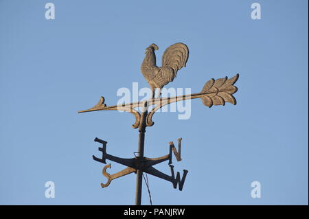 Directional weather vane in the form of a rooster marking north, south, east and west, with arrow with feathers, atop which the rooster stands, USA. - Stock Image