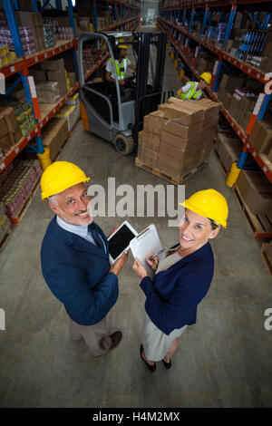 Warehouse manager and client holding digital tablet and clipboard - Stock Image