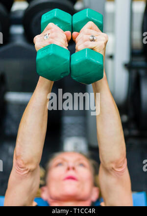 50 yr old female body builder training in a gym - Stock Image