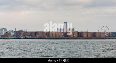 Liverpool, England, UK - November 4, 2015: Liverpool's gothic cathedral towers over the city skyline and warehouses of the Albert Dock as seen from th - Stock Image