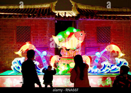 Jinjiang, China's Fujian Province. 17th Feb, 2019. A young visitor poses for photos with a festive lantern at the Wudianshi historical community in Jinjiang, southeast China's Fujian Province, Feb. 17, 2019. More than 3,000 festive lanterns have been set in three dedicated zones in Jinjiang ahead of the Lantern Festival, which falls on Feb. 19 this year and marks the end of the Chinese Lunar New Year celebrations. Credit: Jiang Kehong/Xinhua/Alamy Live News - Stock Image