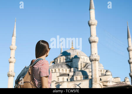 Young adult girl tourist with a backpack sightseeing in Istanbul. Tourist near the Blue mosque. Tourism in Turkey. - Stock Image