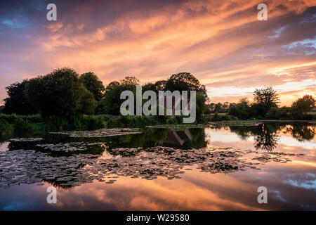 church reflections on a lake during a bright sunset - Stock Image