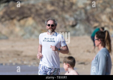 A mature man wearing a t shirt with an amusing slogan jogging along the shoreline on Fistral Beach in Newquay in Cornwall. - Stock Image