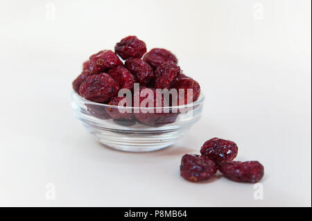 Tasty cranberries in a transparent glass bowl, healthy choice for consumers, or as part of five a day fruit and vegetables consumption - Stock Image
