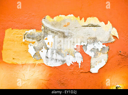 Peeling orange paint on a stone wall, as a background - Stock Image
