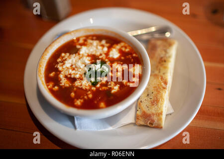 Bowl of Tomato soup with goat cheese and flat bread stick. - Stock Image