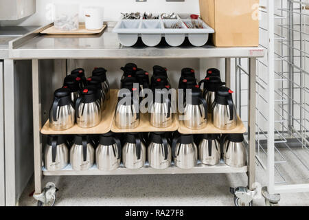 Cutlery and stainless steel insulated water jugs in a hospital ward kitchen. - Stock Image