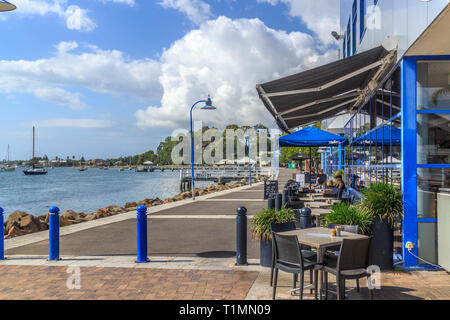 Batemans Bay, Australia - 12th February 2018: People drinking coffee in the sunshine. The promenade is a popular spot. - Stock Image