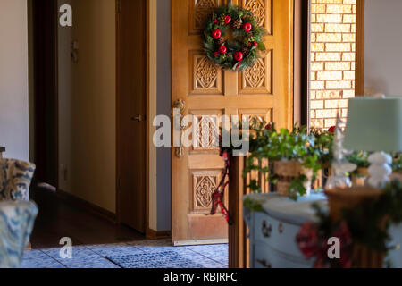 Christmas wreath on a door from inside. - Stock Image