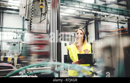 An industrial woman engineer with headset in a factory, working. Copy space. - Stock Image