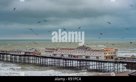 view of the sea at Brighton pier in stormy weather at sunset - Stock Image