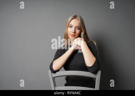 serene young woman sitting astride on chair - gray background with copy space - Stock Image