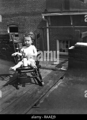 A toddler relaxes on a rooftop in a period wooden rocking chair,  ca. 1925. - Stock Image